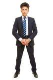 Hombre de negocios que se coloca frontal en un traje fotografía de archivo