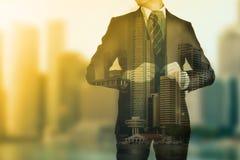 Hombre de negocios que se coloca para mirar su negocio del éxito Foto de archivo libre de regalías