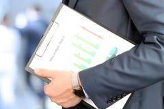 Hombre de negocios que se coloca y que se considera gráfico en su mano Fotografía de archivo libre de regalías