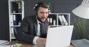 Hombre de negocios que se divierte mientras que escucha y canta música en el lugar de trabajo almacen de video