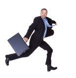 Hombre de negocios que se ejecuta con la cartera a disposición Imagenes de archivo