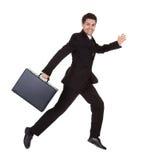 Hombre de negocios que se ejecuta con su cartera Foto de archivo libre de regalías