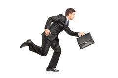 Hombre de negocios que se ejecuta con una cartera Imágenes de archivo libres de regalías