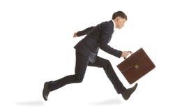 Hombre de negocios que se ejecuta con una cartera Imagen de archivo libre de regalías