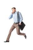 Hombre de negocios que se ejecuta y que habla por el teléfono foto de archivo