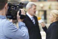 Hombre de negocios que se entrevista con de Recording Female Journalist del cameraman Imagen de archivo