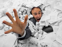 Hombre de negocios que se hunde en el montón de documentos Imagen de archivo libre de regalías
