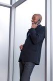 Hombre de negocios que se inclina contra la ventana, hablando fotos de archivo libres de regalías