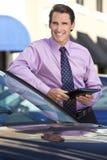 Hombre de negocios que se inclina en el coche con el ordenador de la tablilla Foto de archivo libre de regalías