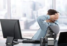 Hombre de negocios que se reclina en el escritorio Imagen de archivo