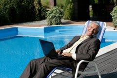 Hombre de negocios que se reclina sobre silla de cubierta Imágenes de archivo libres de regalías