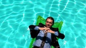 Hombre de negocios que se relaja en el colchón de aire metrajes