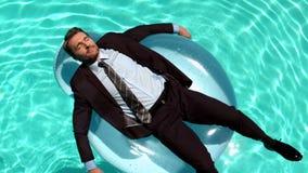Hombre de negocios que se relaja en la boya metrajes