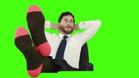 Hombre de negocios que se relaja en su silla con las piernas encima y sin de los zapatos metrajes