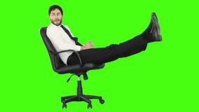 Hombre de negocios que se relaja en su silla con las piernas para arriba almacen de metraje de vídeo