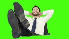 Hombre de negocios que se relaja en su silla con las piernas para arriba almacen de video