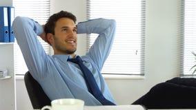 Hombre de negocios que se relaja mientras que en el trabajo metrajes