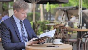 Hombre de negocios que se sienta al aire libre Reading Book almacen de metraje de vídeo