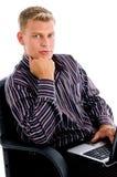 Hombre de negocios que se sienta con la reclinación de la computadora portátil y de la barbilla Foto de archivo libre de regalías
