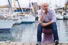 Hombre de negocios que se sienta en barcos y yates costosos de navegación en el A.C. foto de archivo