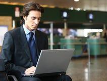 Hombre de negocios que se sienta en el aeropuerto b Foto de archivo libre de regalías