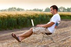 Hombre de negocios que se sienta en el campo y que trabaja en el ordenador portátil fotografía de archivo