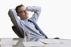 Hombre de negocios que se sienta en el escritorio - aislado Imagenes de archivo