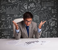 Hombre de negocios que se sienta en el escritorio con esquema y los iconos del negocio Imagen de archivo libre de regalías