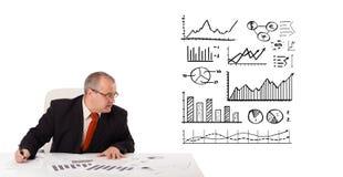 Hombre de negocios que se sienta en el escritorio con estadísticas y gráficos foto de archivo libre de regalías