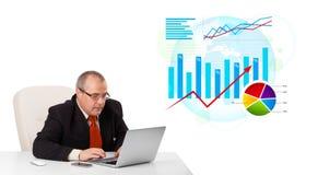 Hombre de negocios que se sienta en el escritorio con la computadora portátil y estadísticas Fotografía de archivo