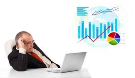 Hombre de negocios que se sienta en el escritorio con la computadora portátil y estadísticas Imagenes de archivo
