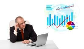 Hombre de negocios que se sienta en el escritorio con la computadora portátil y estadísticas Imagen de archivo