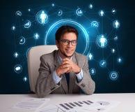 Hombre de negocios que se sienta en el escritorio con los iconos sociales de la red Imágenes de archivo libres de regalías