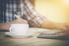 Hombre de negocios que se sienta en el escritorio de oficina con la taza de café foto de archivo libre de regalías