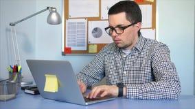 Hombre de negocios que se sienta en el escritorio en la oficina, trabajando en el ordenador portátil almacen de video