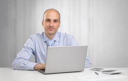 Hombre de negocios que se sienta en el escritorio en oficina Fotos de archivo libres de regalías
