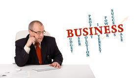 Hombre de negocios que se sienta en el escritorio y que pulsa en el teclado Imagen de archivo libre de regalías