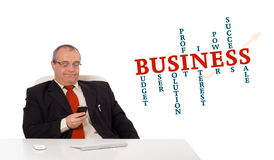 Hombre de negocios que se sienta en el escritorio y que sostiene un móvil con busin Imagenes de archivo
