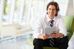Hombre de negocios que se sienta en el sofá en oficina usando la tablilla de Digitaces Fotografía de archivo libre de regalías