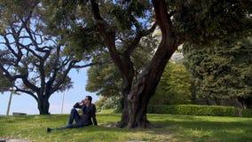 Hombre de negocios que se sienta en hierba y que habla en el smartphone, relajación en parque metrajes