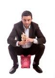 Hombre de negocios que se sienta en la hucha que cuenta euros del dinero Imagen de archivo