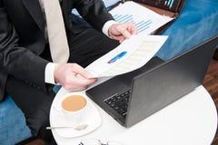 Hombre de negocios que se sienta en la oficina detrás del escritorio y del análisis de ventas comprobado Fotos de archivo