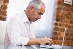 Hombre de negocios que se sienta en la oficina que pulsa en la computadora portátil Foto de archivo