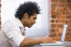 Hombre de negocios que se sienta en la oficina que pulsa en la computadora portátil Imagen de archivo