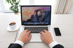 Hombre de negocios que se sienta en la retina de MacBook Pro con OSX Yosemite Imagen de archivo