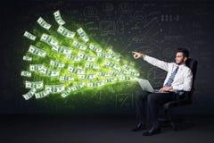 Hombre de negocios que se sienta en la silla que sostiene el ordenador portátil con los billetes de dólar co Imagen de archivo libre de regalías