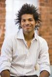 Hombre de negocios que se sienta en la sonrisa del espacio de oficina Fotos de archivo libres de regalías