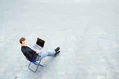 Hombre de negocios que se sienta en la tabla afuera Fotografía de archivo libre de regalías