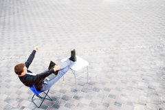 Hombre de negocios que se sienta en la tabla afuera Foto de archivo libre de regalías