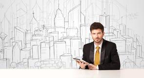 Hombre de negocios que se sienta en la tabla blanca con los edificios dibujados mano Fotos de archivo libres de regalías